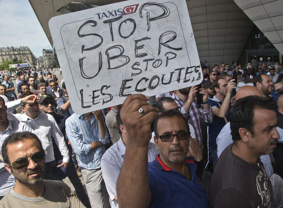 "A striking taxi driver holds a placard which read, ""Stop Uber, Stop listening,"" referring to the new US spying report in France, during a taxi drivers demonstration in Paris, France, Thursday, June 25, 2015. French taxis are on strike around the country, snarling traffic in major cities and slowing access to Paris' Charles de Gaulle airport after weeks of rising and sometimes violent tensions over Uber. (AP Photo/Michel Euler)"