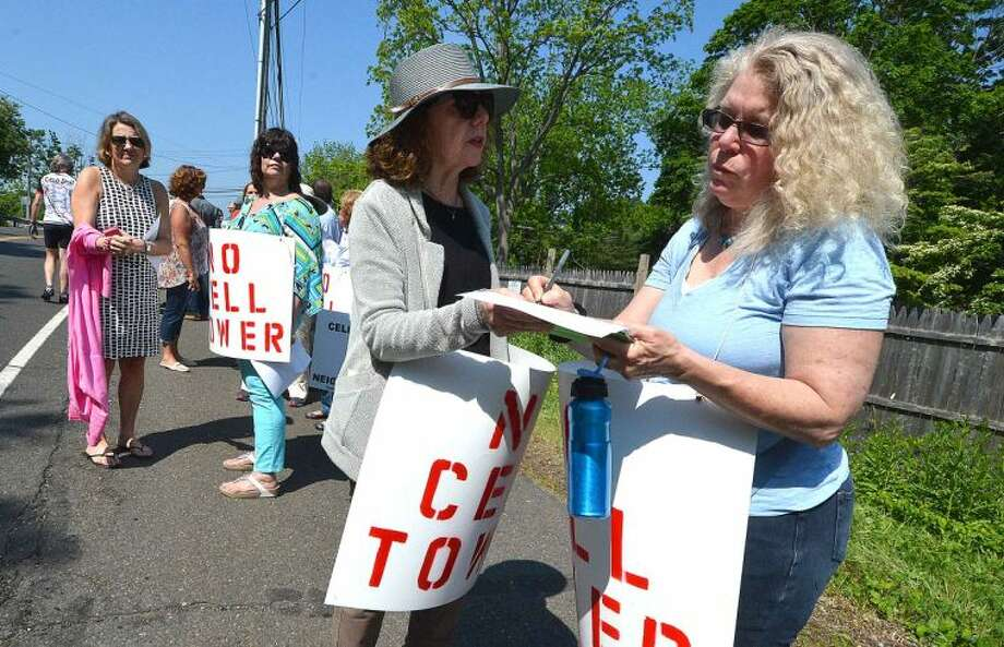 Hour Photo/Alex von Kleydorff Jill Brody passes a petition to Helen Martin Block to sign during a protest of the construction of a 120 foot high cell tower off Greens Farms Rd in Westport