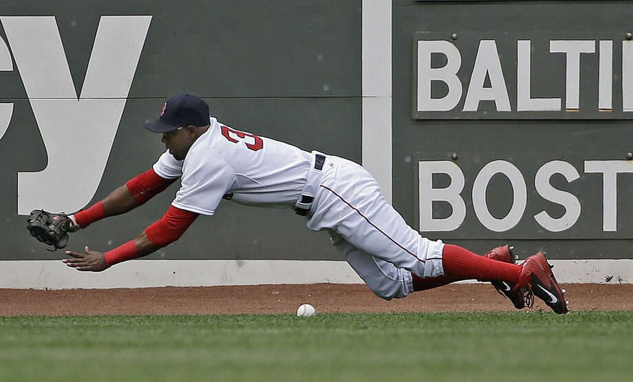 Boston Red Sox right fielder Alejandro De Aza dives but can't come up with an RBI single by Baltimore Orioles' Manny Machado in the sixth inning of a baseball game at Fenway Park, Thursday, June 25, 2015, in Boston. (AP Photo/Elise Amendola)