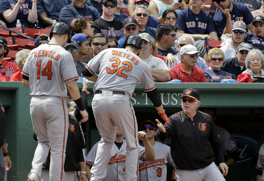 Baltimore Orioles manager Buck Showalter, right, congratulates Matt Wieters (32) after his two-run home run in the fourth inning of a baseball game against the Boston Red Sox, Thursday, June 25, 2015, at Fenway Park in Boston. (AP Photo/Elise Amendola)