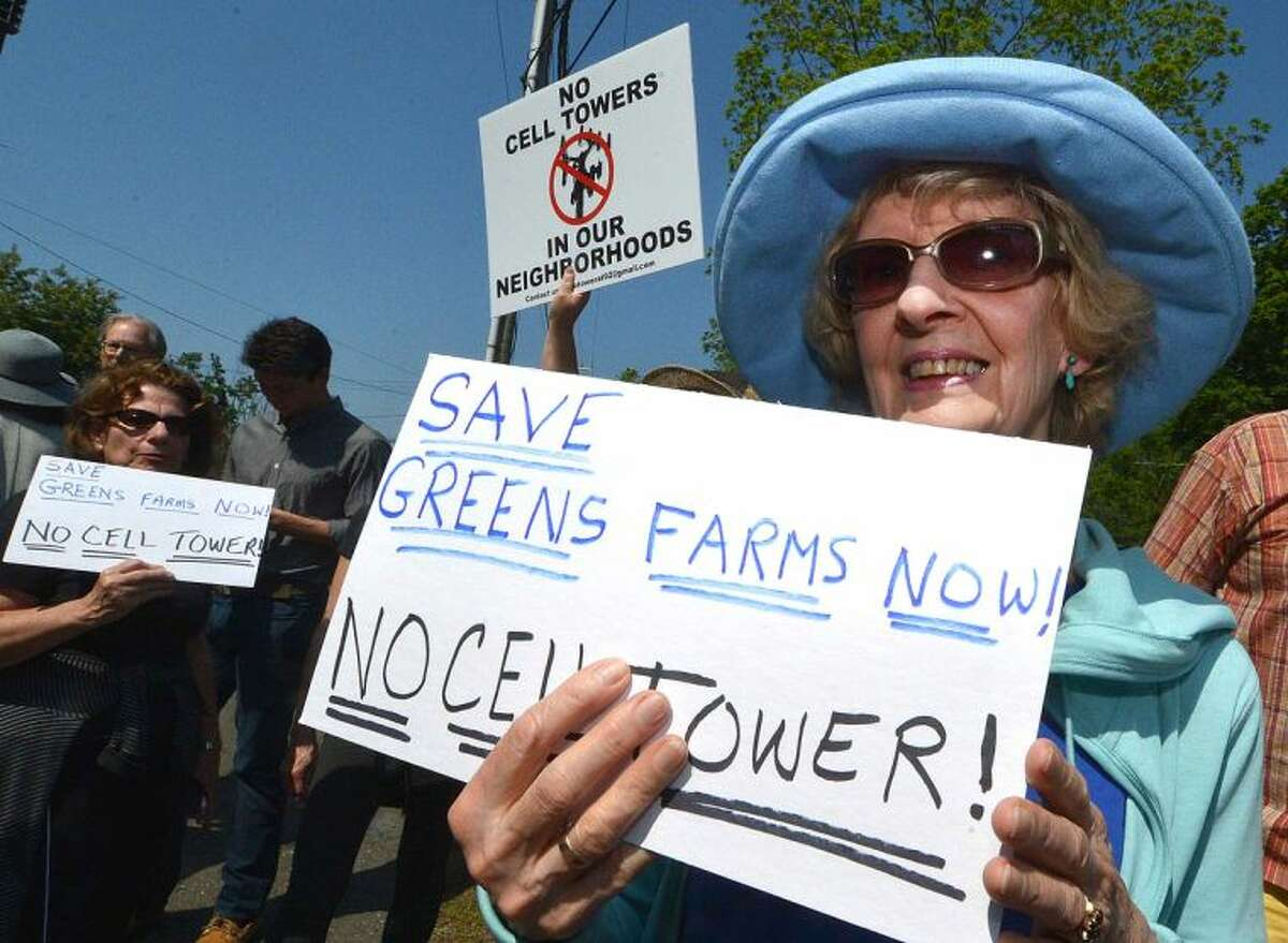 Hour Photo/Alex von Kleydorff Mardy Durham holds a sign in protest with others to the proposal to build a cell tower at the intersections of Greens Farms Rd and Hillspoint in Westport