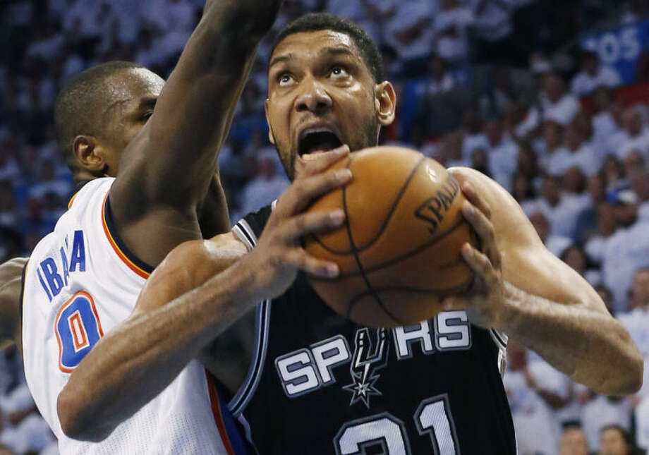 San Antonio Spurs forward Tim Duncan (21) shoots against Oklahoma City Thunder forward Serge Ibaka in overtime of Game 6 of the Western Conference finals NBA basketball playoff series in Oklahoma City, Saturday, May 31, 2014. San Antonio won 112-107 and advanced to the NBA Finals. (AP Photo/Sue Ogrocki)