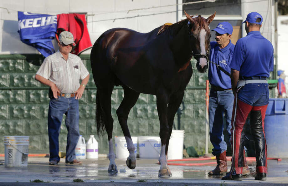 Trainer Art Sherman, left, watches as California Chrome is bathed after a workout at Belmont Park, Tuesday, June 3, 2014, in Elmont, N.Y. The Kentucky Derby and Preakness Stakes winner will attempt to become the first Triple Crown winner since Affirmed in 1978 when he races in the146th running of the Belmont Stakes on Saturday. (AP Photo/Julie Jacobson)