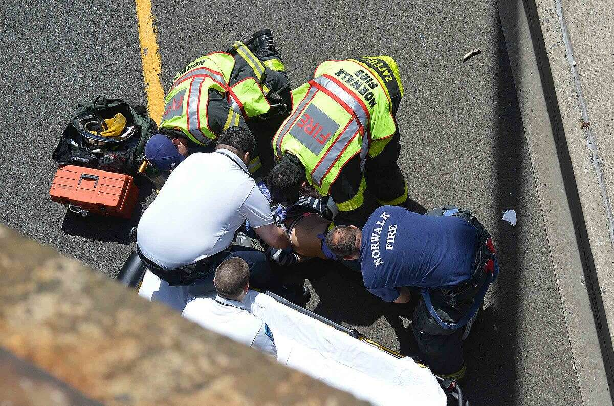 Hour Photo/Alex von Kleydorff First responders attend to a woman who fell from the Scribner Ave overpass onto Interstae 95 northbound around 2:30 pm on Wednesday