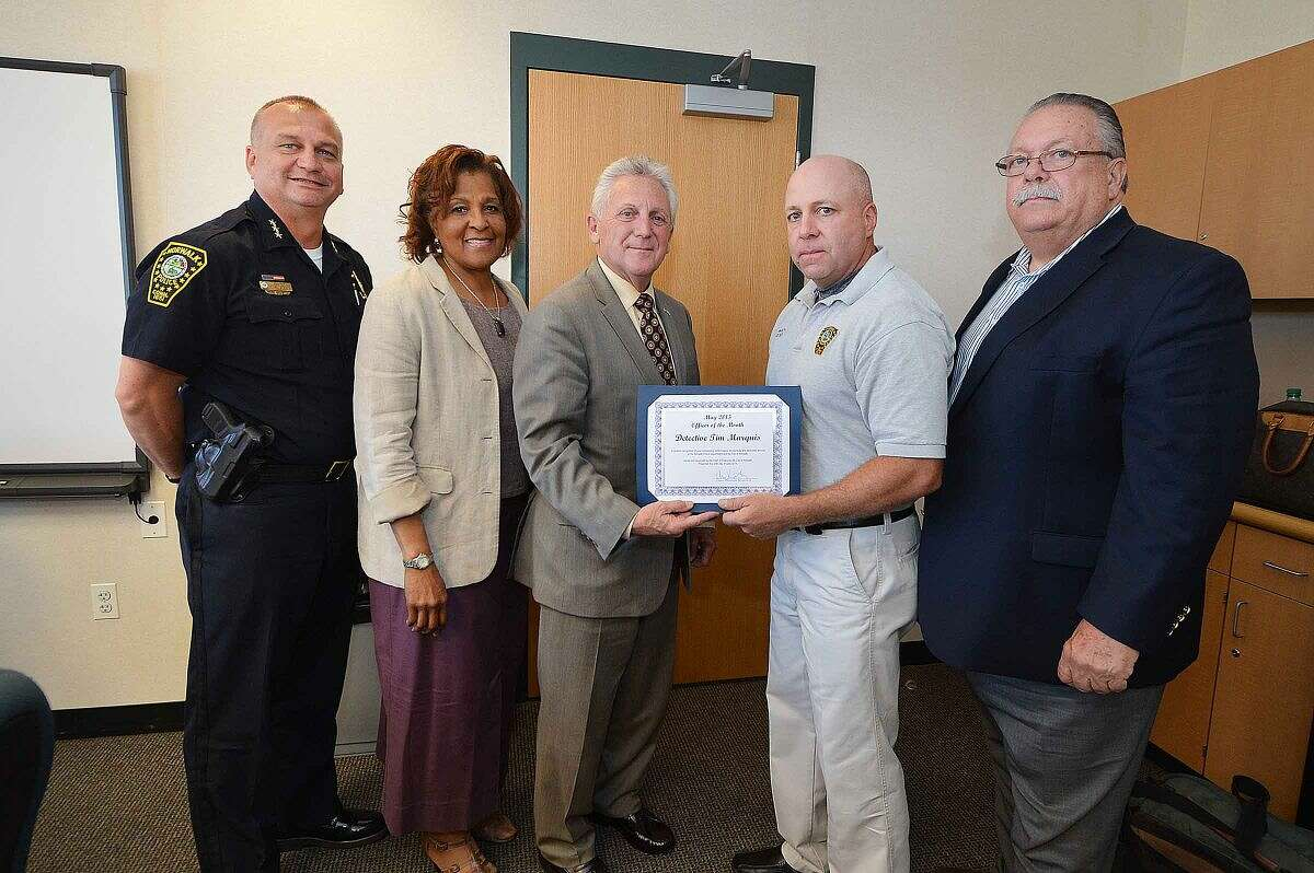 Hour photo/Alex von Kleydorff Mayor Harry Rilling hands an award to Officer of the Month Tim Marquis as Police Chief Thomas Kulhawik, from left, Police Commissioner Fran Collier-Clemens, and Police Commissioner Charlie Yost, far right, look on during the Police Commission meeting Wednesday.