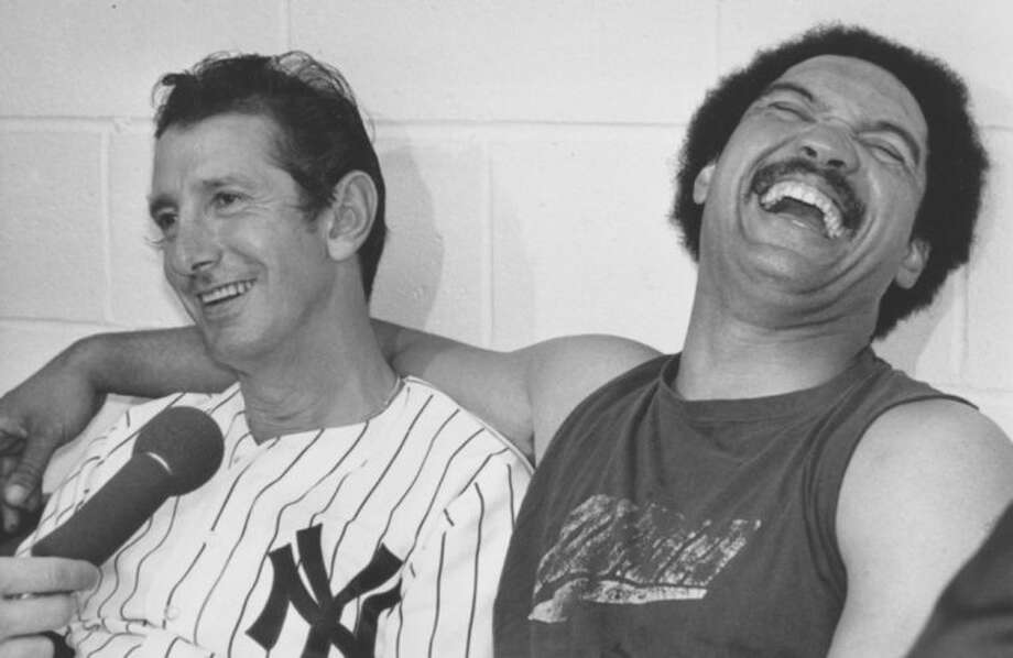 FILE - In this Oct. 18, 1977 file photo, New York Yankees manager Billy Martin, left, and slugger Reggie Jackson laugh during a post-victory news conference at New York's Yankee Stadium. Jackson clinched the World Series championship for the Yankees in game six against the Los Angeles Dodgers with an unprecented three consecutive homers in a series game. It's been 33 years since teams from these cities played for a title. The rivalry could be lost on many fans when the Kings and Rangers meet for the Stanley Cup. (AP Photo/File)