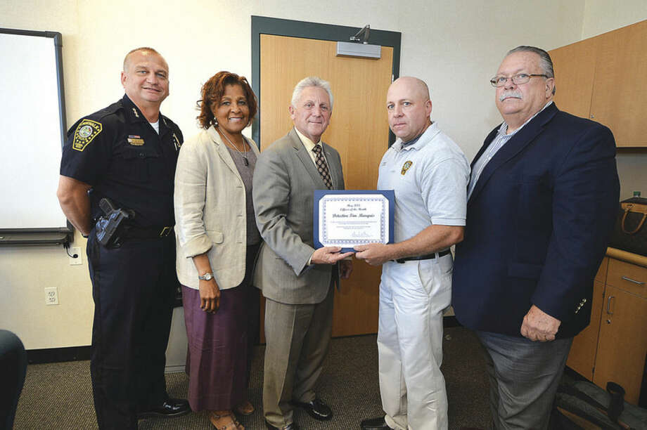 Hour photo/Alex von KleydorffMayor Harry Rilling hands an award to Officer of the Month Tim Marquis as Police Chief Thomas Kulhawik, from left, Police Commissioner Fran Collier-Clemens, and Police Commissioner Charlie Yost, far right, look on during the Police Commission meeting Wednesday.