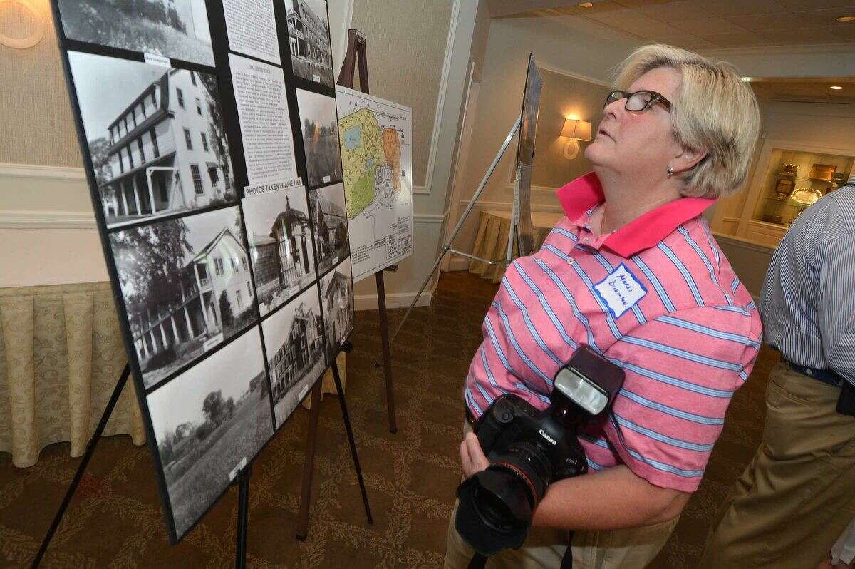 Hour Photo/Alex von Kleydorff. Mardi Dickinson looks at a board that has photos of some of the structures that once stood on the Manresa property from 1887-1952 during the meeting of the Manresa Association at Shore and Country Club
