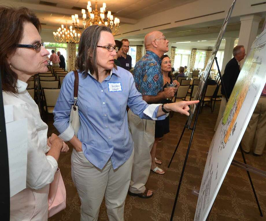 Hour Photo/Alex von Kleydorff. Kristen Hoyt and Ellen Mitten look at a map of the Manresa property and the power plant during the Manresa Association meeting at Shore and Country Club