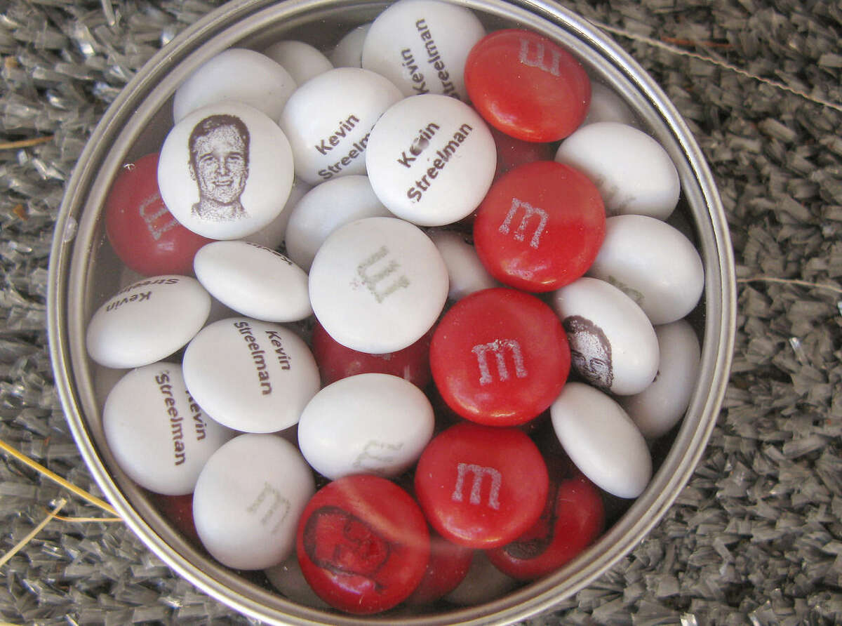 This personalized tin of M&M candies printed with the face and name of 2014 Travelers Golf Championship winner Kevin Streelman is seen Wednesday, June 24, 2015 in Cromwell, Conn. The tournament, which begins Thursday, has become known for the little perks it offers golfers, including giving the champion a supply of personalized M&Ms. (AP Photo/Pat Eaton-Robb)