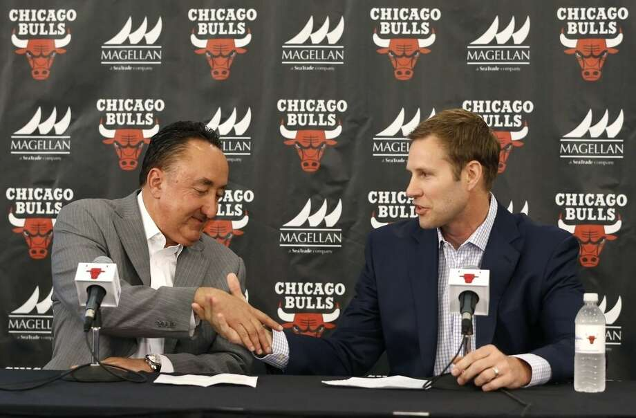FILE - In this June 2, 2015, file photo, Chicago Bulls general manager Gar Forman, left, shakes hands with Fred Hoiberg after introducing him as the team's new coach during an NBA basketball news conference, in Chicago. The Bulls own the 22nd pick in Thursday's NBA draft. And with a deep pool of guards, drafting a backup for Derrick Rose could be the way they go. (AP Photo/Charles Rex Arbogast, File)