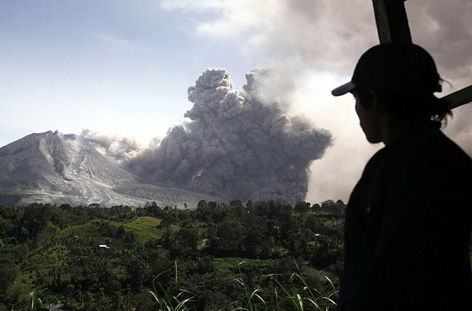A man watches as Mount Sinabung releases a pyroclastic flow in Tiga Pancur, North Sumatra, Indonesia, Wednesday, June 24, 2015. The volcano has been put at its highest alert level since June 2 following significant increase in its activity. (AP Photo/Binsar Bakkara)