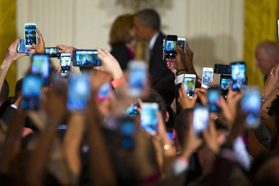 Guests hold up cell phones as President Barack Obama, right, is greeted by White House chief technology officer Megan Smith as he arrives for a reception to celebrate LGBT Pride Month in the East Room of the White House, on Wednesday, June 24, 2015, in Washington. (AP Photo/Evan Vucci)