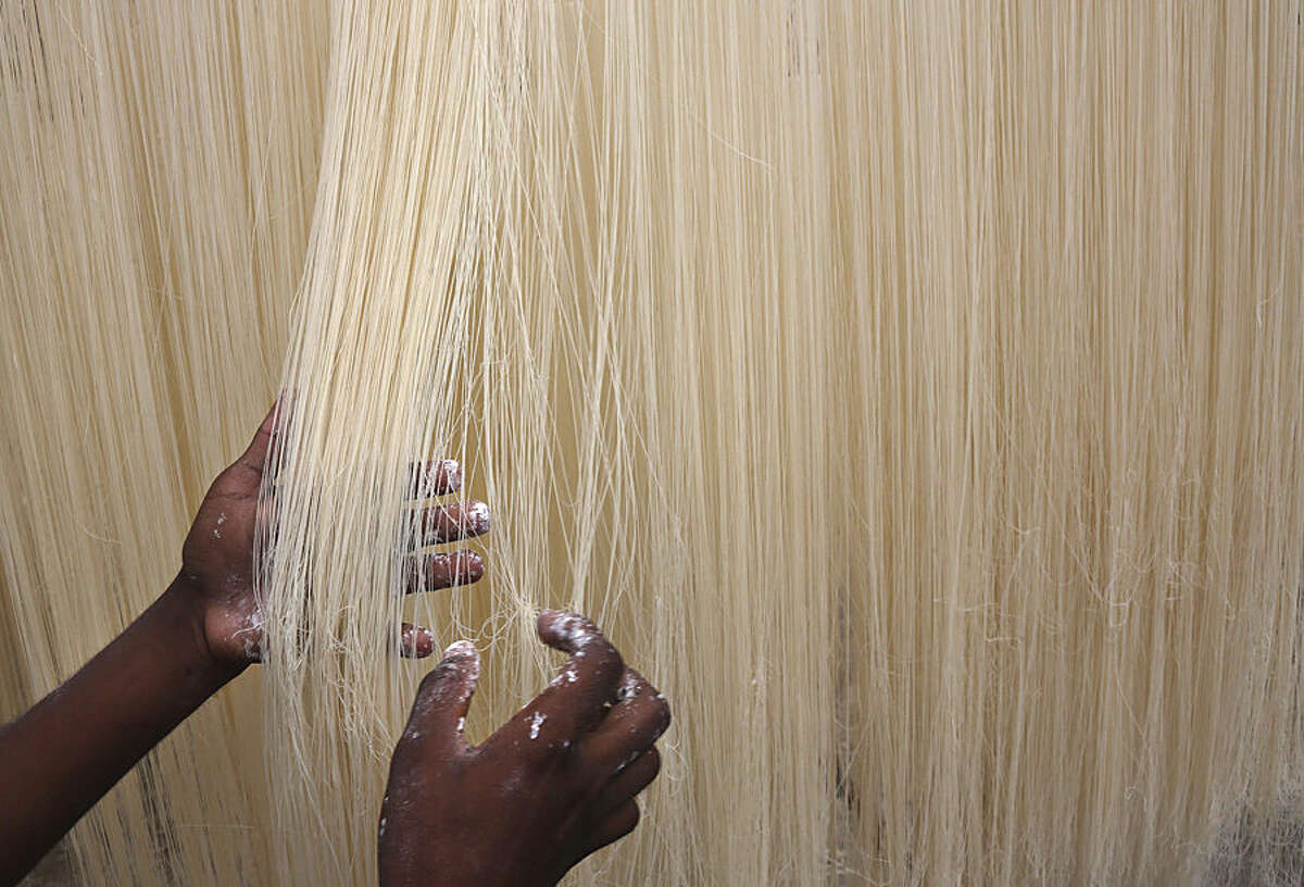 An Indian worker hangs strands of vermicelli to sun dry in Hyderabad, India, Thursday, June 25, 2015. Vermicelli is in great demand among Muslims when they break their daylong fast during the holy month of Ramadan. (AP Photo/Mahesh Kumar A.)
