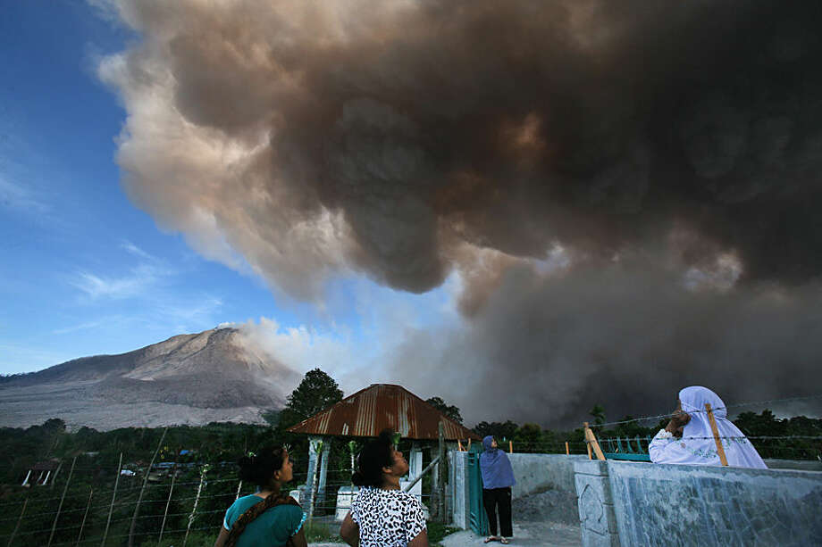 Villagers watch as Mount Sinabung releases volcanic material into the air in Tiga Serangkai, North Sumatra, Indonesia, Thursday, June 25, 2015. The volcano has spewed hot lava almost daily since its alert status was raised early this month to the highest level. Thousands of villagers whose homes are in the danger zone have been evacuated since then to safer areas. (AP Photo/Binsar Bakkara)