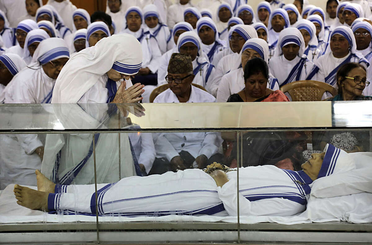 A senior nun pays tribute as others gather for a mass prayer ceremony near the casket of Sister Nirmala Joshi at the Missionaries of Charity in Kolkata, India, Wednesday, June 24, 2015. The Indian nun who replaced Mother Teresa as head of the Missionaries of Charity died Tuesday, June 23, the organization said. Sister Nirmala Joshi was 81. (AP Photo/Bikas Das)