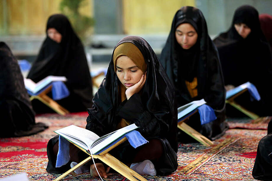 Iranian worshipers recite verses of the Quran, Islam's holy book, during the Muslim holy fasting month of Ramadan at the shrine of Saint Mohammad Helal Ibn Ali in the city of Aran and Bidgol, some 140 miles (225 kilometers) south of the capital Tehran, Iran, Wednesday, June 24, 2015. Muslims throughout the world are marking Ramadan - a month of fasting during which the observants abstain from food, drink and other pleasures from sunrise to sunset. (AP Photo/Ebrahim Noroozi)