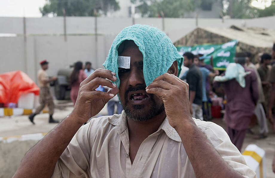 A man covers his head with a wet towel to avoid heatstroke in Karachi, Pakistan, Wednesday, June 24, 2015. A cool wind from the sea and pre-monsoon rains brought the first signs of respite to southern Pakistan on Wednesday as the death toll from a scorching heat wave climbed to over 800, a high figure even for a nation accustomed to sizzling hot summers. (AP Photo/Shakil Adil)