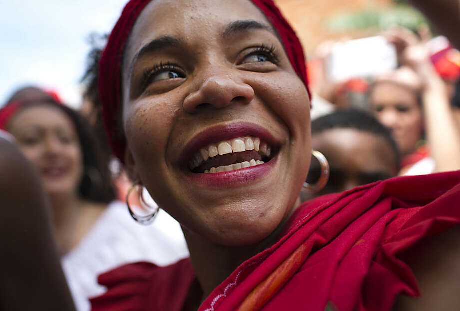 A woman smiles as she dances during the San Juan festivities in Curiepe, Miranda State, Venezuela, Wednesday, June 24, 2015. This celebration is joined by hundreds of devotees who will sing, dance and pray to the beat of drums that never stop ringing. The celebration commemorates Saint John the Baptist and according to tradition the feast is the time when slaves where allowed to rest for three days in June. (AP Photo/Ariana Cubillos)