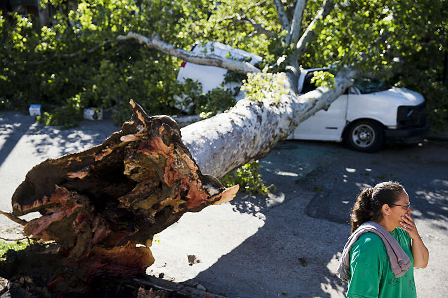 Elsie Yambo inspects damage on Sylvester Street in the aftermath of a storm Wednesday, June 24, 2015, in Philadelphia. Powerful storms that plowed through eastern Pennsylvania and New Jersey downed trees and power lines, leaving nearly 400,000 without electricity and disrupting mass transit service in both states Wednesday. (AP Photo/Matt Rourke)
