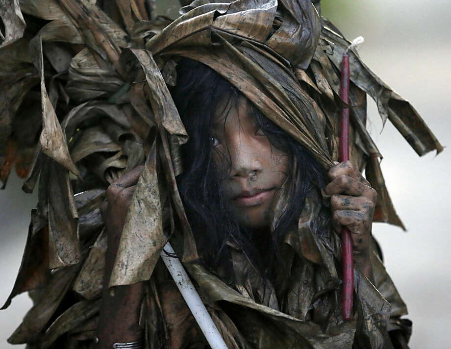 A muddied girl, donning a cape made of dried banana leaves, collects candles before attending a mass to celebrate the Feast Day of St. John the Baptist in the village of Bibiclat, Aliaga township, Nueva Ecija province in northern Philippines,Wednesday, June 24, 2015. At dawn every June 24th, people from Bibiclat village in the northern Philippines' Nueva Ecija province pay homage to their patron saint, John the Baptist, by gathering in silence in a swampy field to cover themselves in mud, donning mud-drenched capes made of dried banana leaves. (AP Photo/Bullit Marquez)