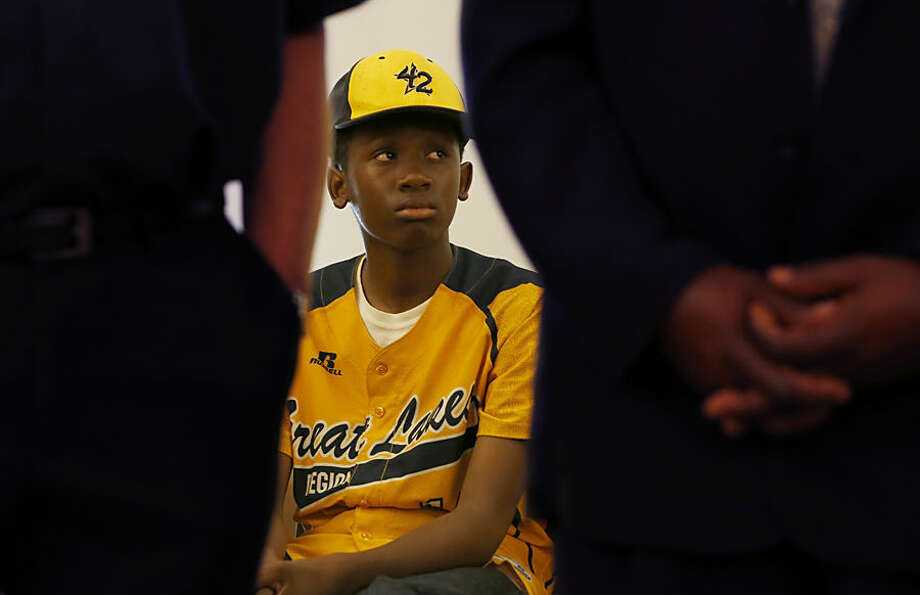 Jackie Robinson West Little League baseball team player Cameron Bufford listens as team attorney Victor Henderson addresses members of the media at a news conference Wednesday, June 24, 2015, in Chicago. Henderson announced a lawsuit Wednesday against the sport's governing body, accusing it of improperly stripping it of the national title that had catapulted the young athletes to hometown hero status. (AP Photo/Charles Rex Arbogast)