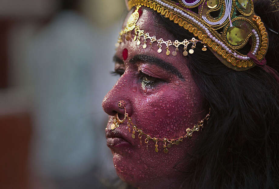 Indian woman Anjali Mahanta, 48, sweats, as she stands dressed as Hindu goddess Kali anticipating alms from devotees at the Kamakhya Hindu temple during the annual Ambubasi festival in Gauhati, India, Wednesday, June 24, 2015. Hundreds of Hindu holy men have arrived here to perform rituals during the five-days long festival that began Monday. (AP Photo/ Anupam Nath)