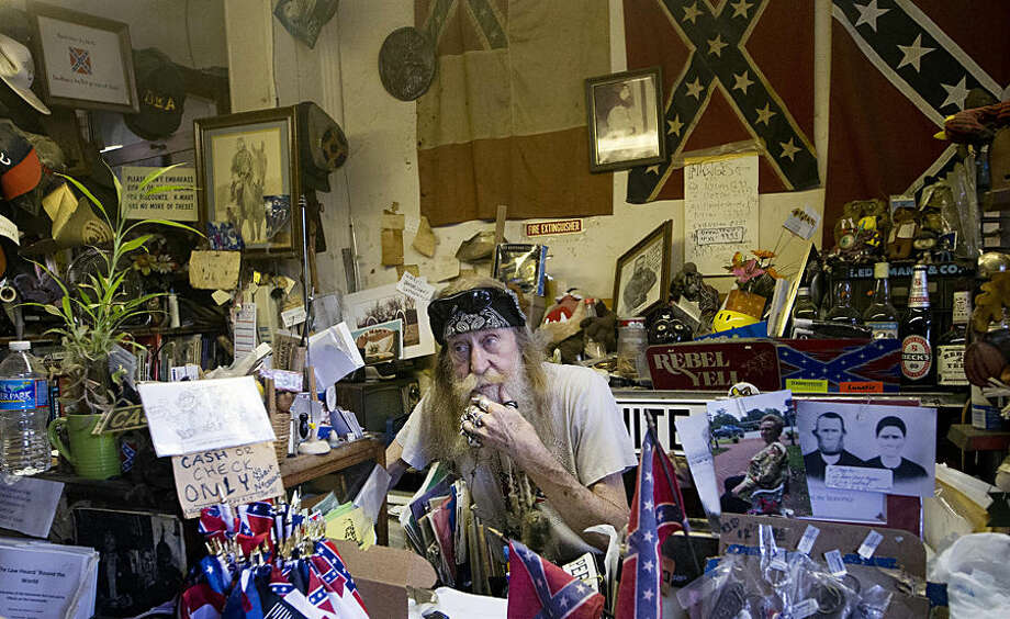 Dent Myers works behind the counter at his store Wildman's, Wednesday, June 24, 2015, in Kennesaw, Ga. The store sells Confederate and Civil War items. (AP Photo/John Bazemore)