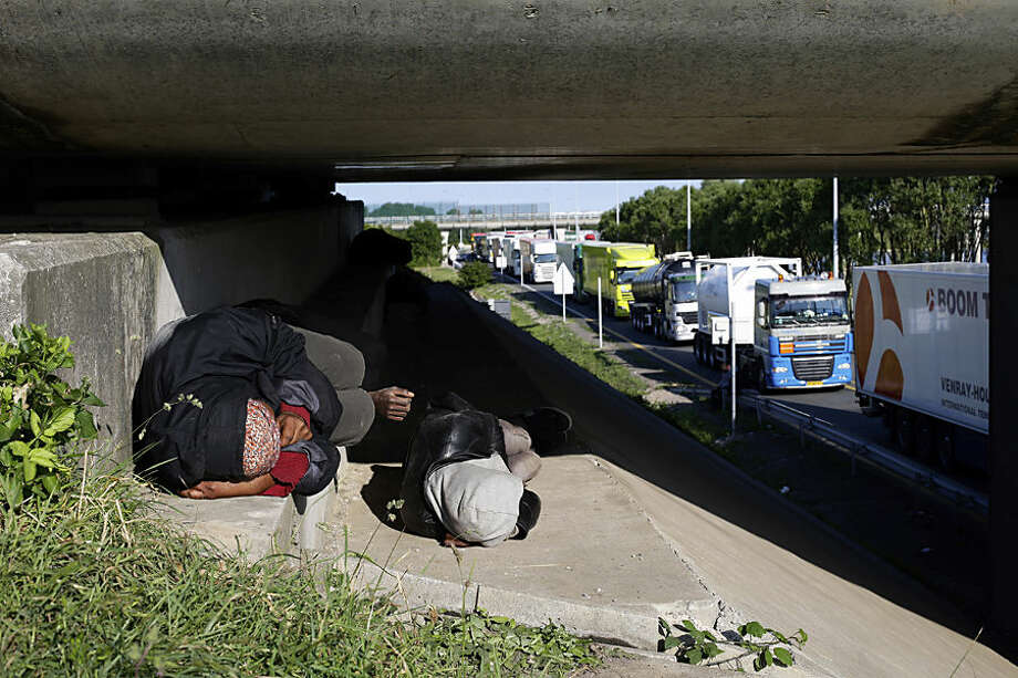 Migrants sleep along a motorway leading to a ferry port to cross the English Channel, in Calais, northern France, Wednesday, June 24, 2015. All trains and many ferry services between Britain and France were cut off Tuesday by striking port workers, stranding hundreds of trucks and thousands of passengers on both sides of the English Channel. Adding to the chaos, illegal migrants who are camped by the thousands in the port city of Calais were seen trying to stowaway on vehicles stuck in traffic jams. (AP Photo/Thibault Camus)