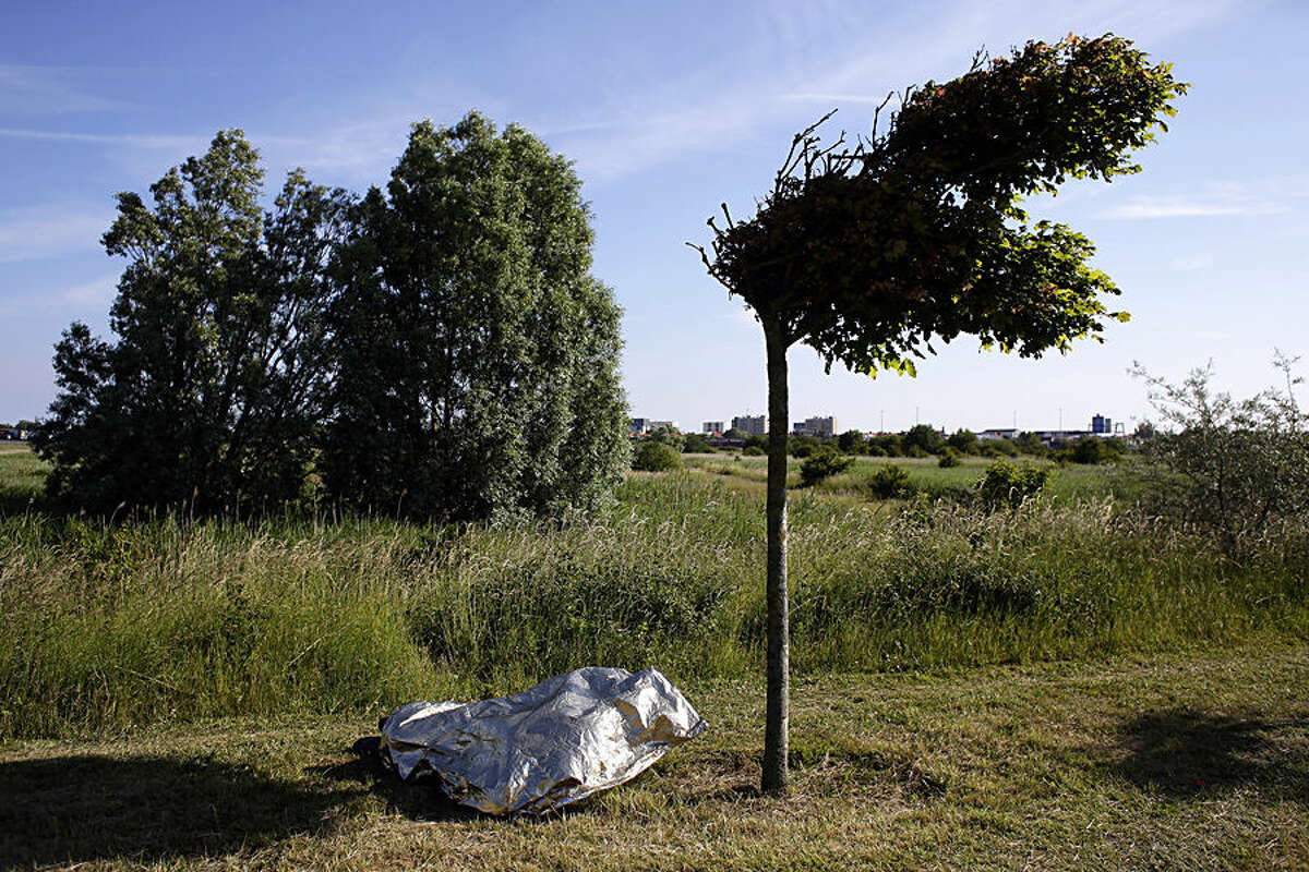 A migrant sleeps under a life blanket, along a motorway leading to a ferry port to cross the English Channel, in Calais, northern France, Wednesday, June 24, 2015. All trains and many ferry services between Britain and France were cut off Tuesday by striking port workers, stranding hundreds of trucks and thousands of passengers on both sides of the English Channel. Adding to the chaos, illegal migrants who are camped by the thousands in the port city of Calais were seen trying to stowaway on vehicles stuck in traffic jams. (AP Photo/Thibault Camus)