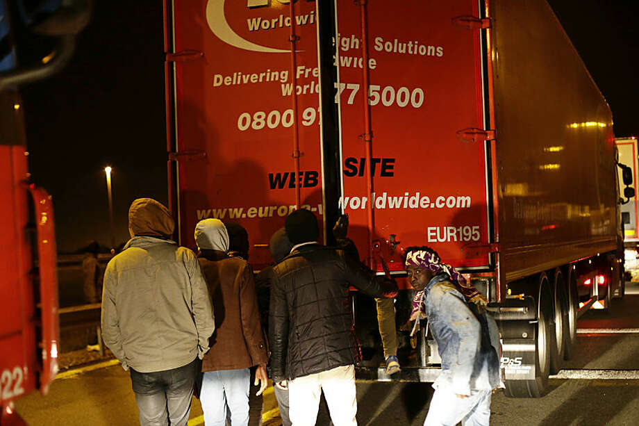 Migrants open a lorry in a failed attempt to cross the English Channel, in Calais, northern France, Wednesday, June 24, 2015. All trains and many ferry services between Britain and France were cut off Tuesday by striking port workers, stranding hundreds of trucks and thousands of passengers on both sides of the English Channel. Adding to the chaos, illegal migrants who are camped by the thousands in the port city of Calais were seen trying to stowaway on vehicles stuck in traffic jams. (AP Photo/Thibault Camus)