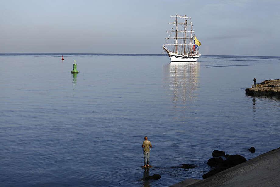 A man fishes in the Havana Harbor as Venezuela's Simon Bolivar school sailing ship arrives to Havana, Cuba, Wednesday, June 24, 2015. (AP Photo/Desmond Boylan)