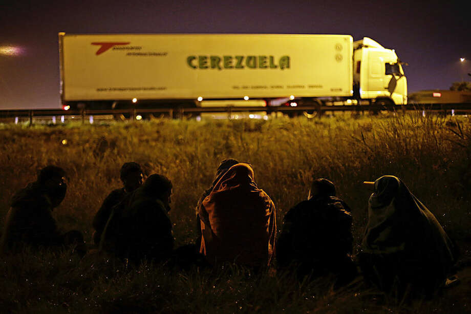 Migrants wait along a motorway leading to a ferry port to cross the English Channel, in Calais, northern France, Wednesday, June 24, 2015. All trains and many ferry services between Britain and France were cut off Tuesday by striking port workers, stranding hundreds of trucks and thousands of passengers on both sides of the English Channel. Adding to the chaos, illegal migrants who are camped by the thousands in the port city of Calais were seen trying to stowaway on vehicles stuck in traffic jams. (AP Photo/Thibault Camus)
