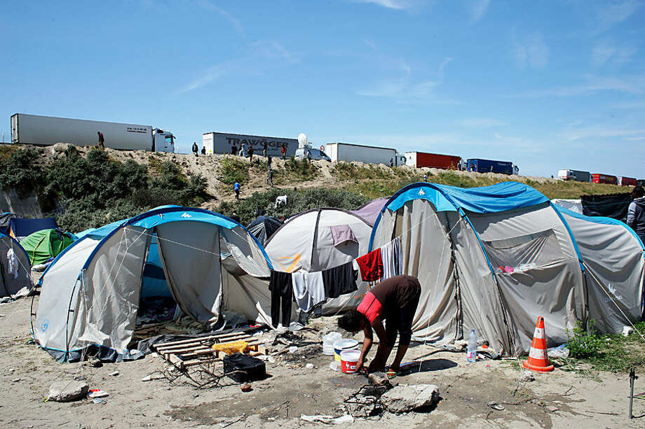 """A migrant washes her feet at a makeshift camp known as the """"jungle"""", in Calais, northern France, Wednesday, June 24, 2015. Train services between Britain and France beneath the English Channel resumed Wednesday but the disruption stoked by striking French port workers the day before persevered. Adding to the chaos, illegal migrants who are camped by the thousands in the port city of Calais were seen trying to stowaway on vehicles stuck in traffic jams. (AP Photo/Thibault Camus)"""