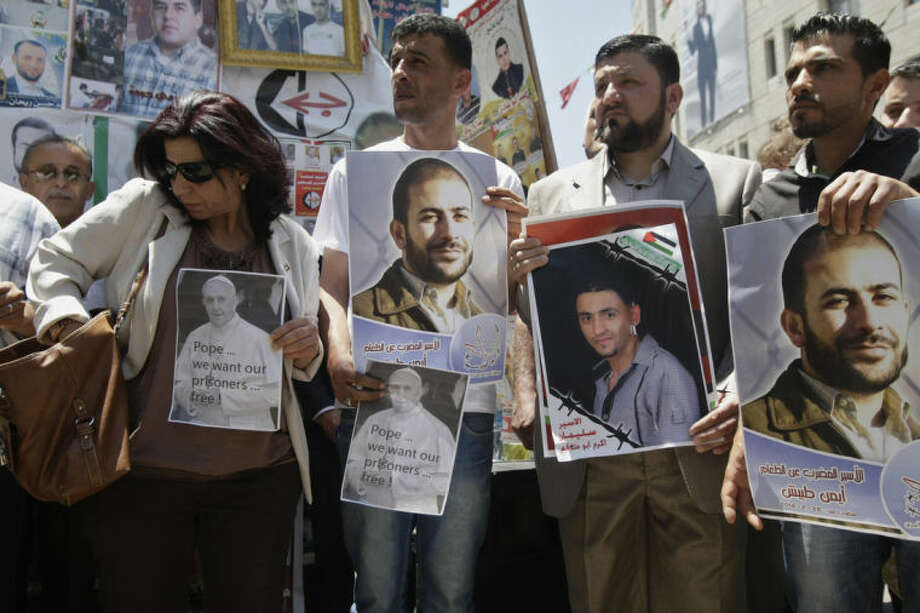 FILE -- In this Sunday, May 25, 2014 file photo, Palestinians hold pictures of Pope Francis and Palestinian prisoners during a demonstration to call for the release of Palestinian prisoners from Israeli jails and to support prisoners who have been on hunger strike, in the West Bank town of Nablus. Faced with the second large-scale Palestinian hunger strike in two years, Israel's government is promoting a bill that would allow a judge to sanction force-feeding if an inmate's life is perceived to be in danger. The country's main doctors' association, says the practice amounts to torture and families of hunger strikers say they support the protest despite the risks. (AP Photo/Nasser Ishtayeh, File)