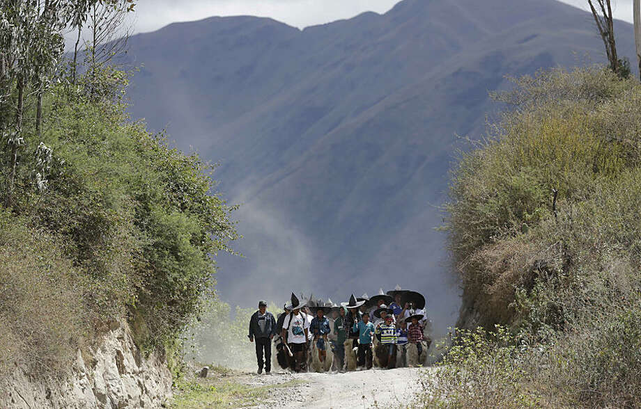 Indians from the province of Imbabura dance on the road on their way to Cotacachi, to to commemorate the day of San Juan in the Catholic tradition and the Inti Raymi or Festival of the Sun in Piabia Chupa, Ecuador, Wednesday, June 24, 2015. All of them arrive in Cotacachi and proceed to the symbolic capture of the main square, where only the police separates the different communities to avoid violence between them. (AP Photo/Dolores Ochoa)