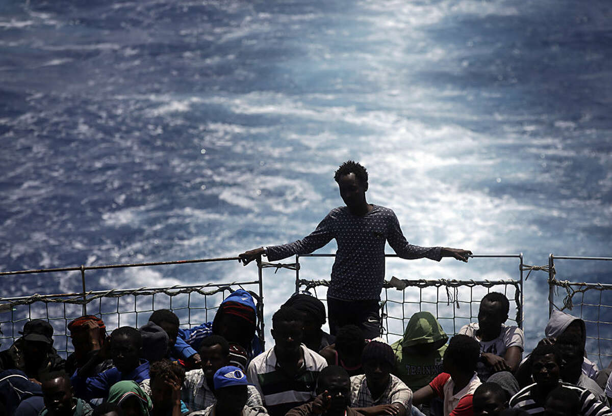 Migrants sit on the deck of the Belgian Navy vessel Godetia after they were saved at sea during a search and rescue mission in the Mediterranean Sea off the Libyan coasts, Wednesday, June 24, 2015. Hundreds of migrants were rescued on Tuesday by the Godetia, which is part of a EU Navy vessels fleet taking part in the Triton migrants rescue operation. (AP Photo/Gregorio Borgia)