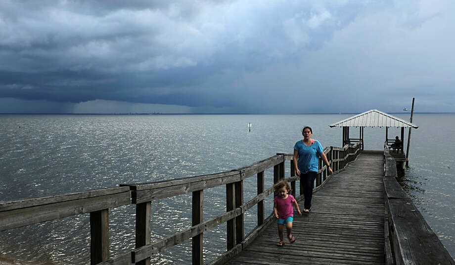 As storm clouds gather over Mobile Bay and rain drops begin to fall, a family leaves a pier Wednesday, June 24, 2015, in Fairhope, Ala. (AP Photo/Kiichiro Sato)