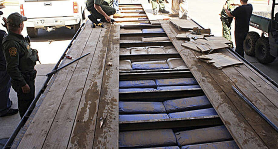 This Monday, June 2, 2014 photo provided by U.S. Customs and Border Protection shows a truck made to look as if it belonged to the U.S. Fish and Wildlife Service, but which was actually carrying more than 3,200 pounds of marijuana, east of Douglas, Ariz. Agents found the truck with the federal agency's decals along the border with Mexico. The driver and a passenger fled from the truck into Mexico after being pulled over by border agents. Agents then discovered that the truck, which had fake decals, was filled with $1.6 million worth of marijuana. (AP Photo/U.S. Customs and Border Patrol)