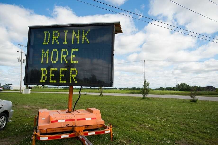"An electronic road sign with the words ""DRINK MORE BEER"" is shown on Tuesday, June 23, 2015, in Frankenlust Township, Mich. An auction company has sold the sign for about $600 after it attracted attention from passers-by with its message. (Yfat Yossifor/The Bay City Times via AP) LOCAL TELEVISION OUT; LOCAL INTERNET"
