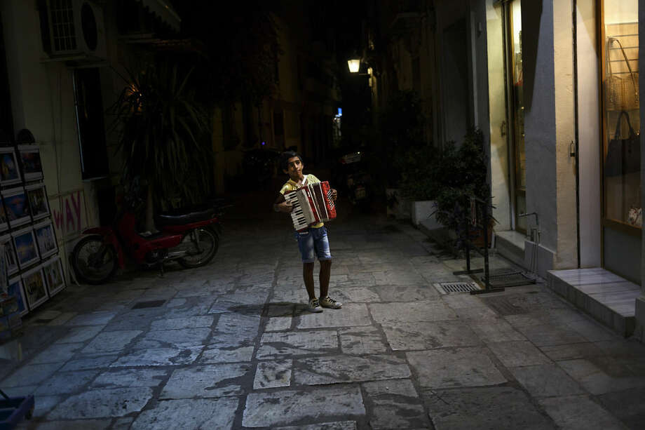 A child plays music for money in the touristic area of Plaka in central Athens, Thursday, June 25, 2015. The ECB approved a request from Athens to increase the amount of emergency liquidity Greek lenders can tap from the country's central bank. Worried Greeks have been withdrawing their money from their country's banks, fearing the imposition of restrictions on banking transactions. An estimated more than 4 billion euros ($4.5 billion) left Greek banks last week. (AP Photo/Daniel Ochoa de Olza)