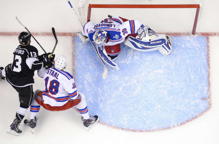 Los Angeles Kings left wing Kyle Clifford, left, scores past New York Rangers defenseman Marc Staal, and goalie Henrik Lundqvist, of Sweden, during the first period in Game 1 of the NHL hockey Stanley Cup Finals, Wednesday, June 4, 2014, in Los Angeles. (AP Photo/Mark J. Terrill)