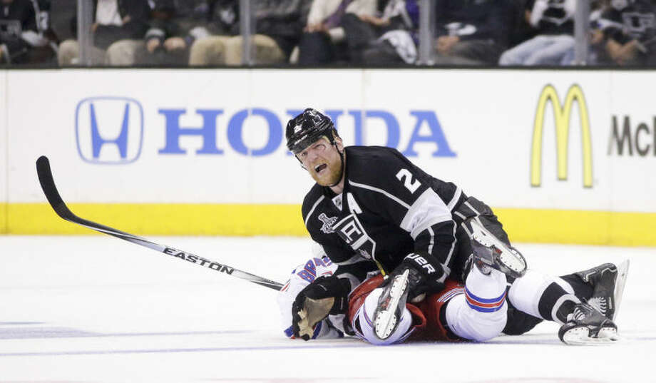 Los Angeles Kings defenseman Matt Greene, top, knocks New York Rangers center Derick Brassard to the ice during the second period of Game 1 in the NHL Stanley Cup Final hockey series on Wednesday, June 4, 2014, in Los Angeles.(AP Photo/Jae C. Hong)