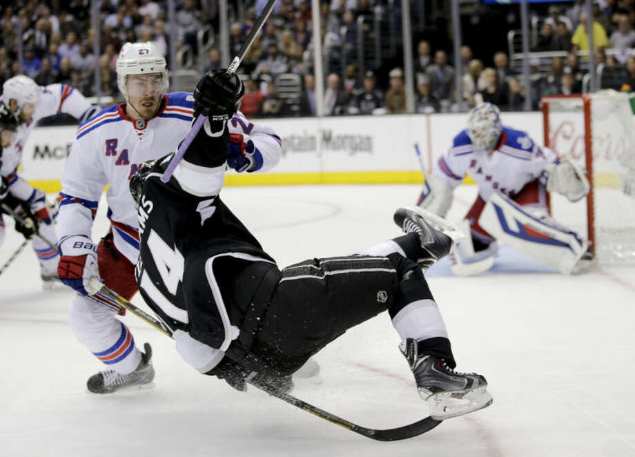 New York Rangers defenseman Ryan McDonagh, left, knocks Los Angeles Kings right wing Justin Williams off his skates during the second period of Game 1 in the NHL Stanley Cup Final hockey series on Wednesday, June 4, 2014, in Los Angeles.(AP Photo/Jae C. Hong)