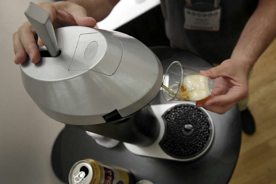 In this Wednesday, June 24, 2015, photo, a Fizzics personal beer dispenser is demonstrated during the CE Week show, in New York. The device, funded by an Indiegogo campaign, takes beer from any store-bought can, bottle or growler and enhances it with a patent-pending fluid and gas technology to give it the bubbles and taste of something straight from the tap. (AP Photo/Richard Drew)