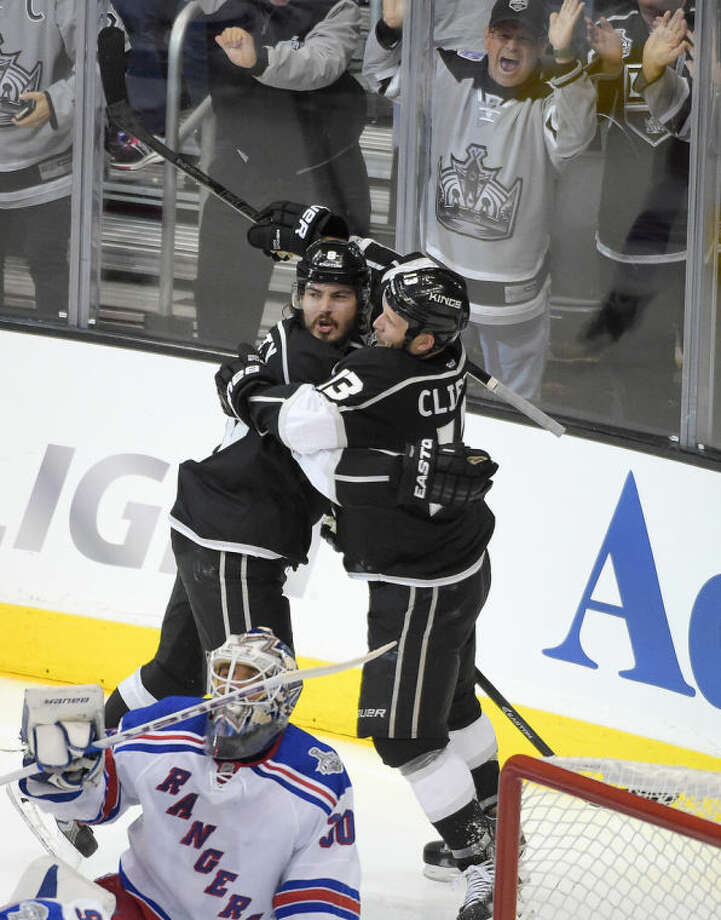 Los Angeles Kings defenseman Drew Doughty, left, celebrates his goal past New York Rangers goalie Henrik Lundqvist, of Sweden, with left wing Kyle Clifford during the second period of Game 1 in the NHL Stanley Cup Final hockey series against the New York Rangers on Wednesday, June 4, 2014, in Los Angeles.(AP Photo/Mark J. Terrill)