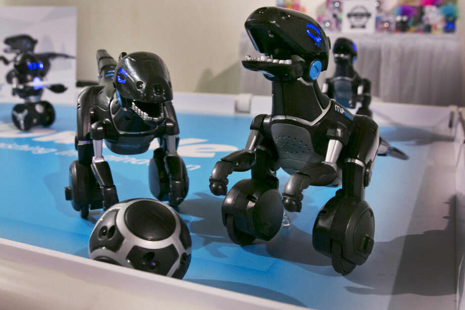In this Wednesday, June 24, 2015, photo, the MiPosaur, from Wowwee, go through their paces during the CE Week show, in New York. Through the use of a form of GPS technology, the mini robots can chase after a matching ball, go for a walk with its owner and even dance and make happy sounds. (AP Photo/Richard Drew)