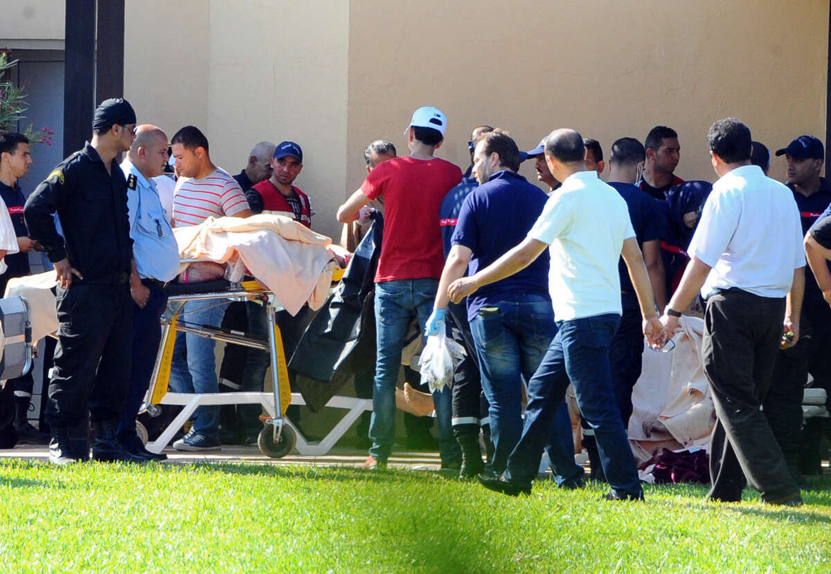 Injured people are treated near the area where an attack took place in Sousse, Tunisia, Friday June 26, 2015. A young man unfurled an umbrella and pulled out a Kalashnikov, opening fire on European sunbathers in an attack that killed at least 28 people at a Tunisian beach resort - one of three deadly attacks from Europe to the Middle East on Friday that followed a call to violence by Islamic State extremists. (AP Photo/Hassene Dridi)