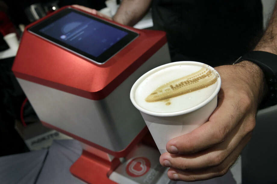 In this June 24, 2015, photo, Israel-based Steam CC demonstrates its $999 Ripples machines during the CE Week show, in New York. The machines combine 3D and ink-jet printer technologies to paint a picture on top of any foam-covered drink using coffee extract. Ripples has inked a deal with Lufthansa to introduce the machines in the airline's first and business-class lounges later this year. (AP Photo/Richard Drew)