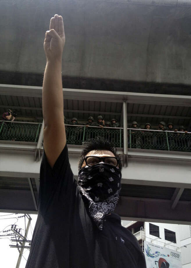 "In this Sunday, June 1, 2014 photo, an anti-coup protester gives a three-finger salute as soldiers keep eyes on him from an elevated walkway near a rally site in central Bangkok, Thailand. Thailand's military rulers say they are monitoring the new form of silent resistance to the coup - borrowed from ""The Hunger Games"" - and will arrest those in large groups who ignore warnings to lower their arms. The raised arm salute has become an unofficial symbol of opposition to Thailand's May 22 coup, and a creative response to several bans the ruling junta has placed on freedom of expression. Some protesters in Thailand say it represents: liberty, equality, fraternity. (AP Photo/Thanyarat Doksone)"
